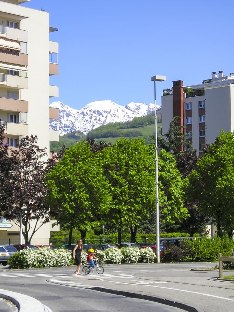 Mother and child crossing the street at Saint-Martin-d'Hères with the snow-capped Alps in background