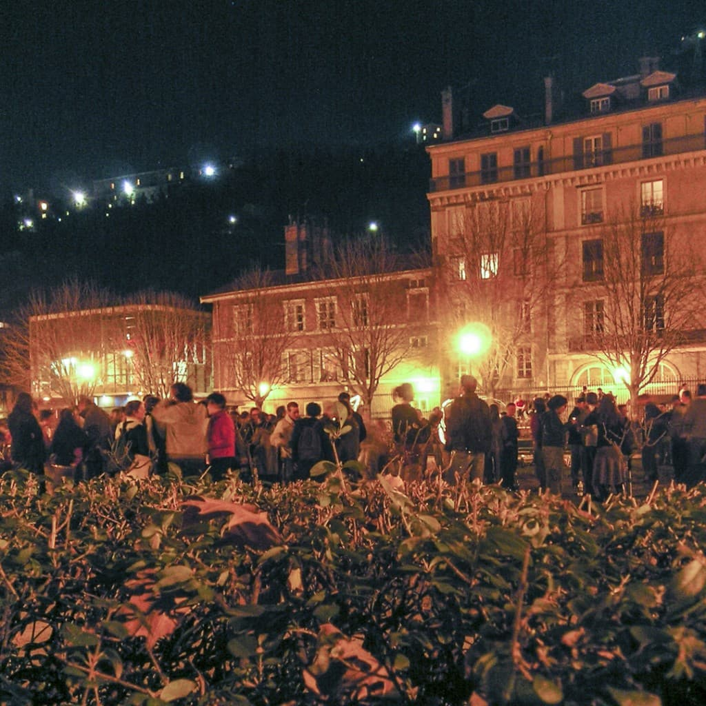 "People socializing and drinking by night at the ""Jardin de Ville"" in Grenoble, France"