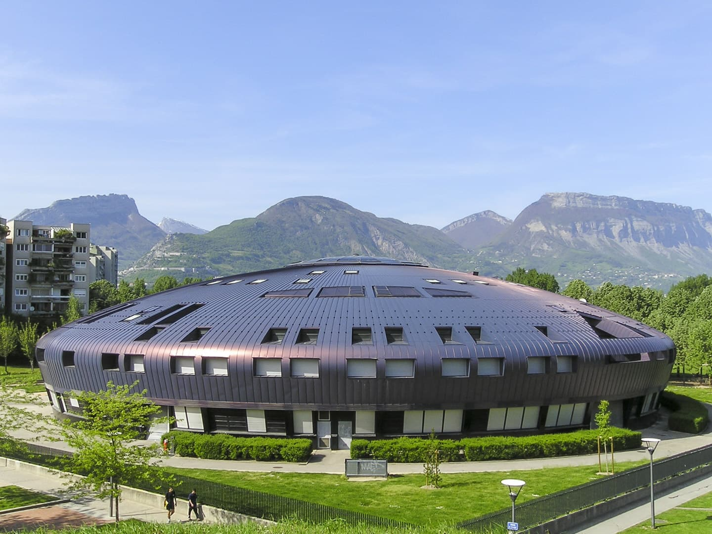 "UFO like ""Lucie Aubrac"" Middle School building in Grenoble (France) with the Alps in the background"