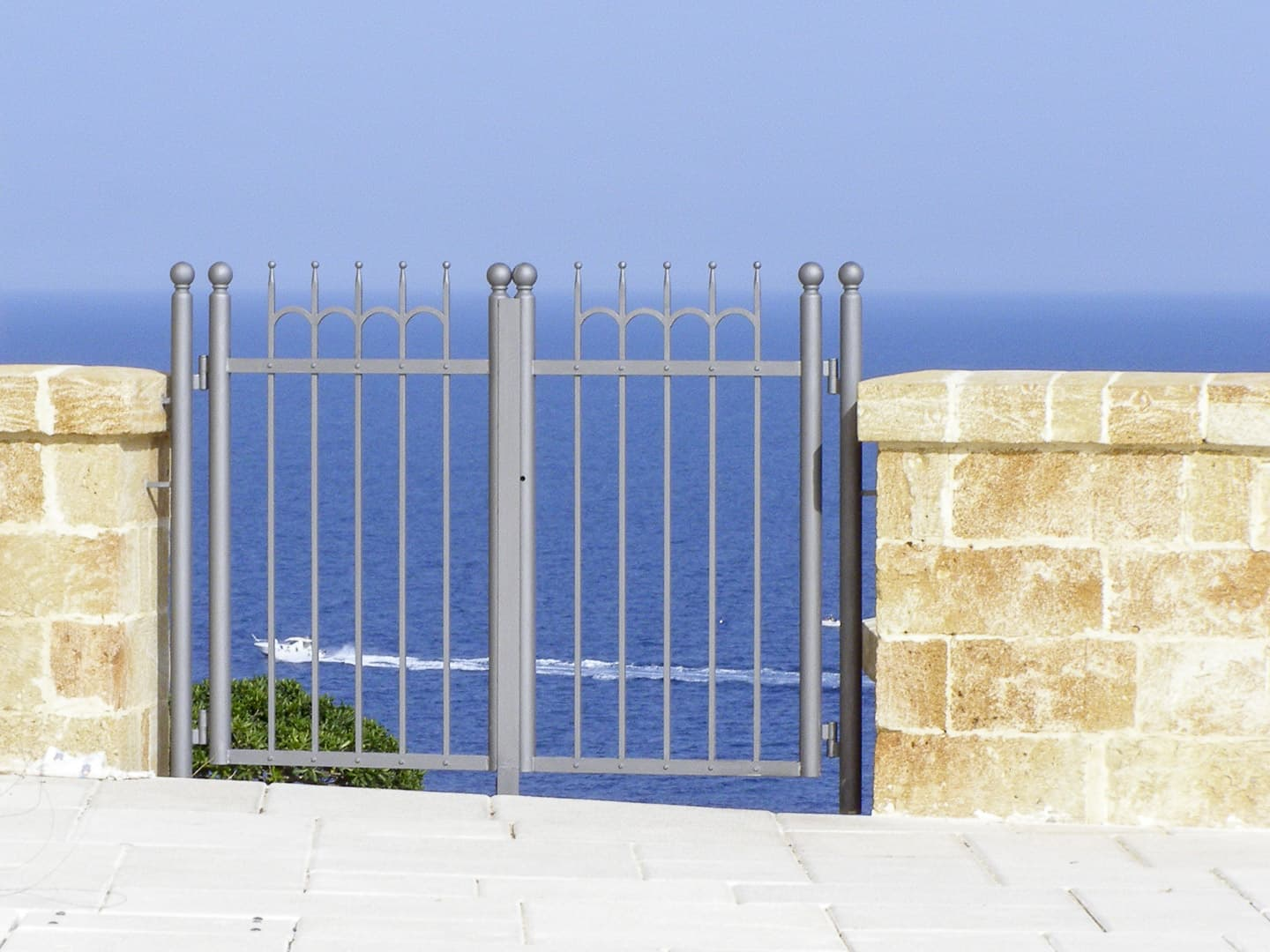 A gate with the sea in the background in Santa Maria di Leuca