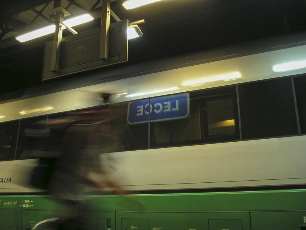 The sign of the train station of Lecce, reflected in the train window