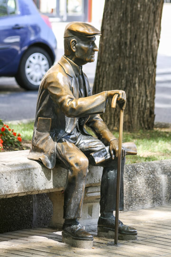 Bronze statue of retired old man sitting on a stone bench at Rambla Nova