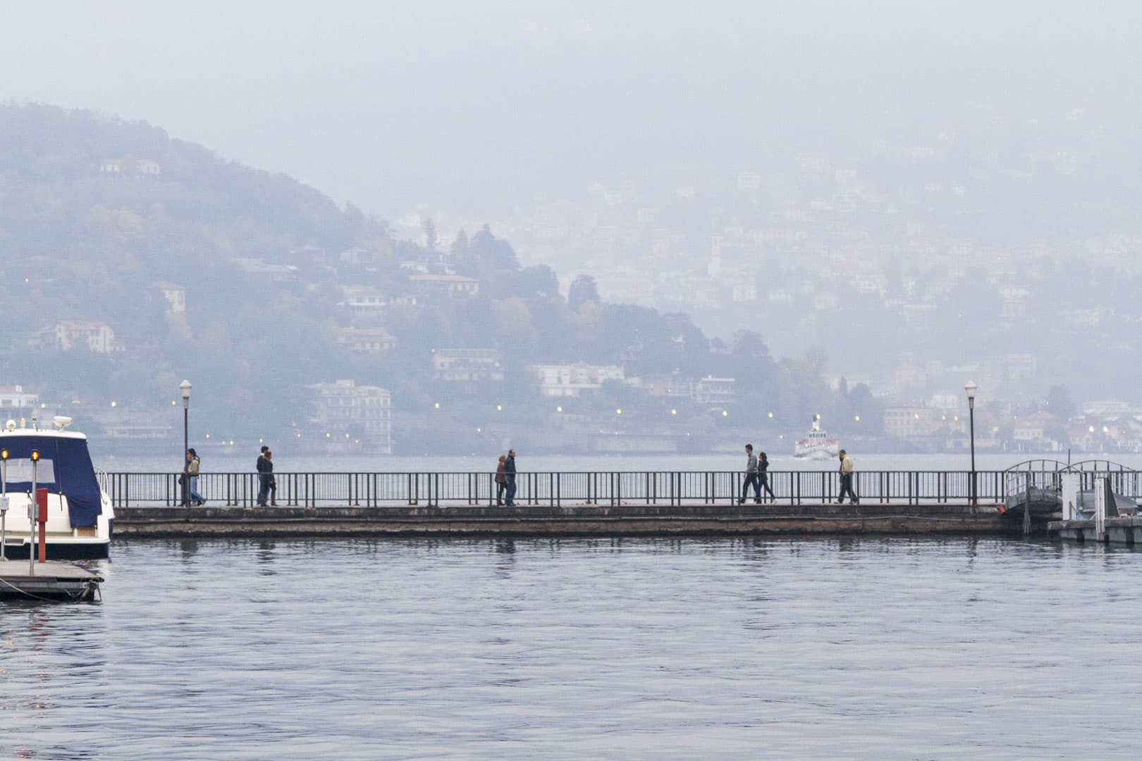 People are Crossing the Bridge Over the Como Lake in Italy-
