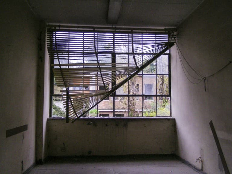 Window at Abandoned Construction Equipment Vehicles Factory in Turin